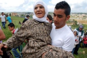 A young Palestinian man in Lebanon carrying his grandmother towards the border on 15-5-2011.(© al-ayyam newspaper)
