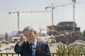 Israeli Prime Minister Benjamin Netanyahu talks as he visits a construction site in the Israeli colony of Har Homa in East Jerusalem, a day ahead of parliamentary elections. Netanyahu is seeking his third consecutive term as premier, his fourth overall. 16 March 2015 (© ASSOCIATED PRESS)